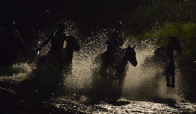 Horses exit the Okanogan River and head up a ramp to the Omak Stampede Rodeo's arena during Friday night's World-Famous Suicide Race.