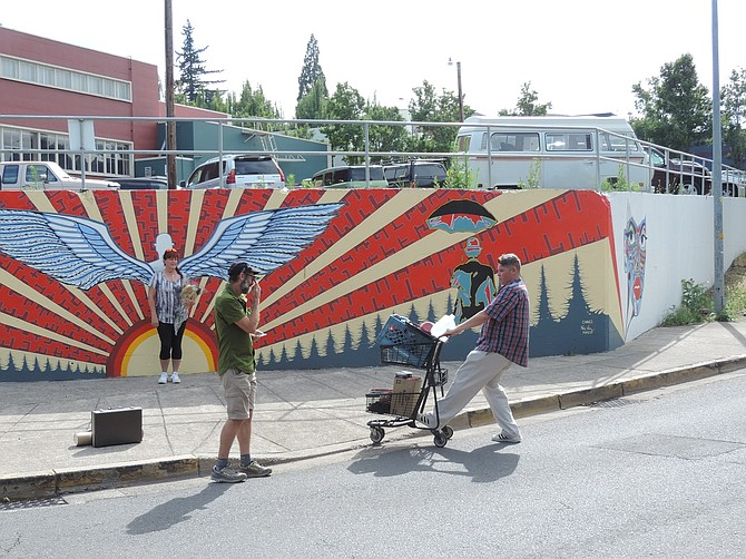 """Mural admirers greet Hood River artist Nate Chavez, right, as he arrives with his paints to work on """"The Remains Mural"""" at Third Street and Industrial Way, in this July 2017 photo."""