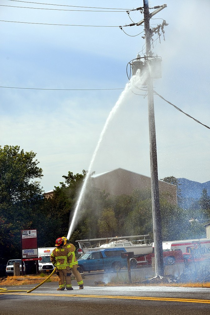 A hose blasts biodegradable suppressant foam on the utility column, stopping any remaining smoke.