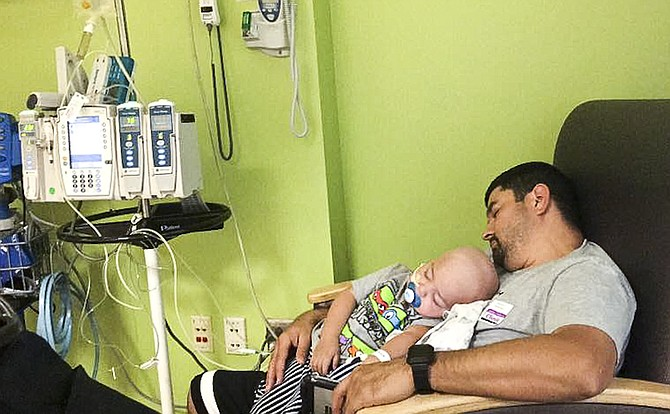Hector Jimenez and his son Jesiah fall asleep together after treatment for Jesiah at Seattle Children's Hospital.