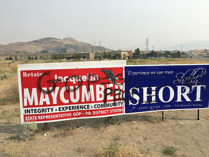 """Campaign signs bear a spray-painted message: """"GOP = greed over people."""""""