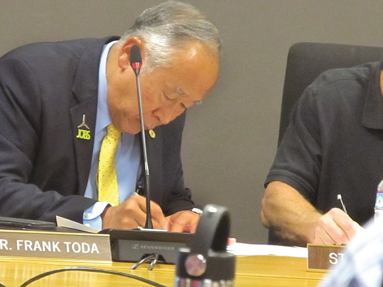 DR. FRANK TODA, president of Columbia Gorge Community College, signs a mutual separation agreement between him and the board of education Wednesday night.