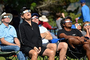SOLAR ECLIPSE: At the Hood River Event Site, campers react to early moments as the sun becomes partially obscured.