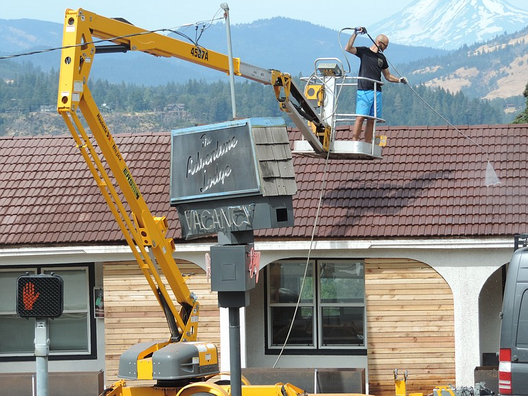 Andreas Ochoa of Rogue Adventures Group power-washes the roof of Hood River Adventure Lodge at Oak and 13th streets as workers prepare for opening on about Sept. 15.