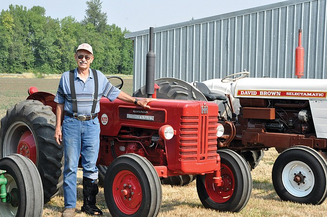 Monmouth resident John Lang stands among his many tractors, leaning against an antique International.