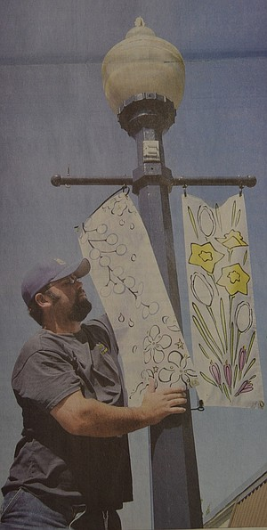August 25, 2007: A Banner Moment — Tucker Nielsen, a member of Hood River's public works crew, hangs the colorful spring and summer banners created by local artist Tara Schifter Kelley. The city held a contest late last winter and selected festive designs for all four seasons. The beautification project is intended to highlight the Urban Renewal work that has been taking place in the downtown business corridor since 1997. Photo by RaeLynn Ricarte.