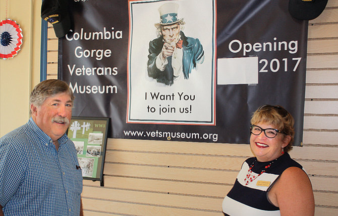 Museum Director Lisa Commander and Wasco County Commissioner Rod Runyon pose in front of a display announcing the opening of the Columbia Gorge Veterans Museum in downtown The Dalles.