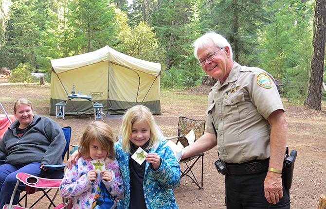 Deputy Jay Waterbury passes out badge stickers to Alivia Calvery, 5, left, and Halee Wisecup, 7, at a Mount Hood Campground.