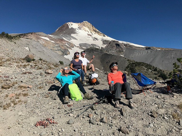 """Watching from up high, not in totality but a great view of the shadow,"" writes Michael Schock of Hood River. ""Beautiful climb through flower filled meadows. As the sky darkened the coyotes went a bit crazy in Heather Canyon."" Pictured are Malcolm and Lisa Brown, Jan Thomson, and Angela Schock."