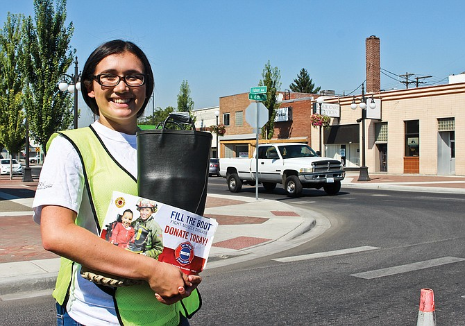 """Sunnyside High School junior Laurissa Ruiz collects donations as part of the Sunnyside Fire Department's annual MDA """"Fill the Boot"""" campaign held in downtown Sunnyside Friday."""