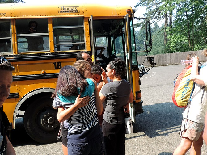 BIRTHDAY girl Maya Merrill hugs her mom, Harumi, as she gets off the bus at Eagle Creek hatchery.