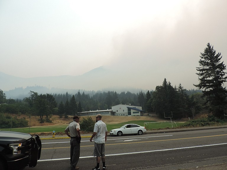 Smoke covers Cascade Locks as deputy Joe Wampler of Hood River County Sheriff's Office talks with Cascade Locks resident Beau Koch on WaNaPa Avenue in front of Cascade Locks School — closed due to the fire on Tuesday, the first day of the new school year.