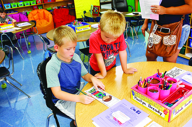 Lyle Elementary School second grader Tristan Howard, left, colors in his bookmark Tuesday morning as his little brother Easton Howard watches. The pair met their teachers and settled into their classrooms during the school's Orientation Day open house.