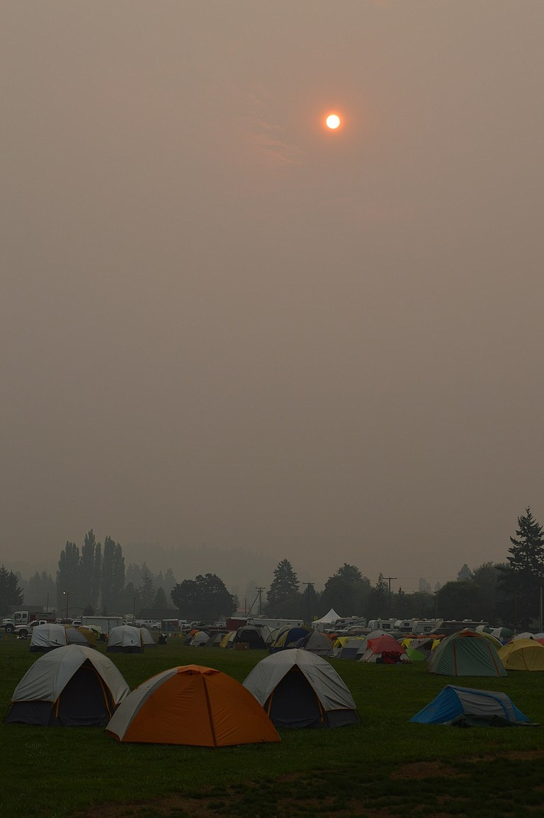 SMOKE obscures the sun and gives a feeling of dusk over fire camp in this scene at Hood River County Fairgrounds Thursday — at 8 a.m.