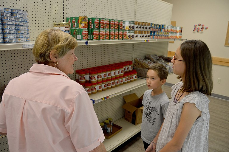 FISH Volunteer Coordinator Billie Stevens explains the shelving system to Leah and Ren Sandahl, who collected cans and bottles this summer in an effort to raise funds for the food bank.