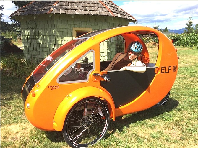 "LEANNE HOGIE draws on solar power and her own strength to travel around the Hood River Valley in a hybrid bicycle-car called an ""ELF."" The Oregon Drive Less Challenge kicks off Friday."