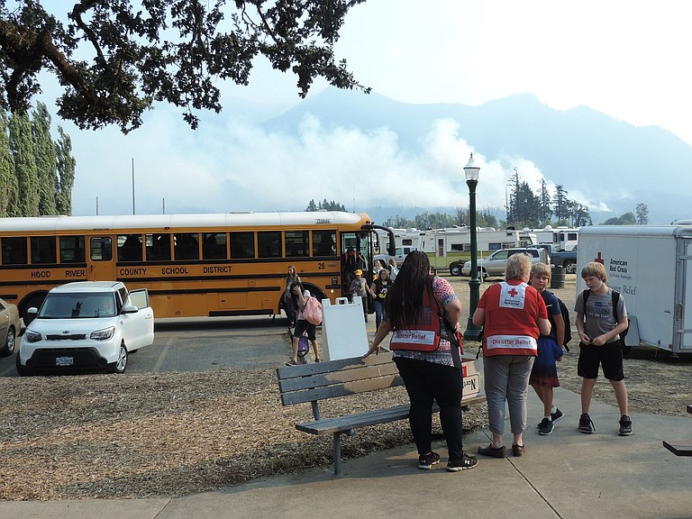 VOLUNTEERS greet Cascade Locks students bussed to temporary quarters Friday after school at Skamania County shelter, as Eagle Creek fire plumes rise across the Columbia.