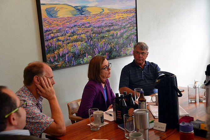 GOV. KATE BROWN speaks to Hood River business leaders at a brief Hood River Hotel stop Thursday morning. Listening are Mayor Paul Blackburn, left, and Sen. Chuck Thomsen, right. Brown heard about economic damage the fire caused. See hoodrivernews.com for details on Brown's visit.