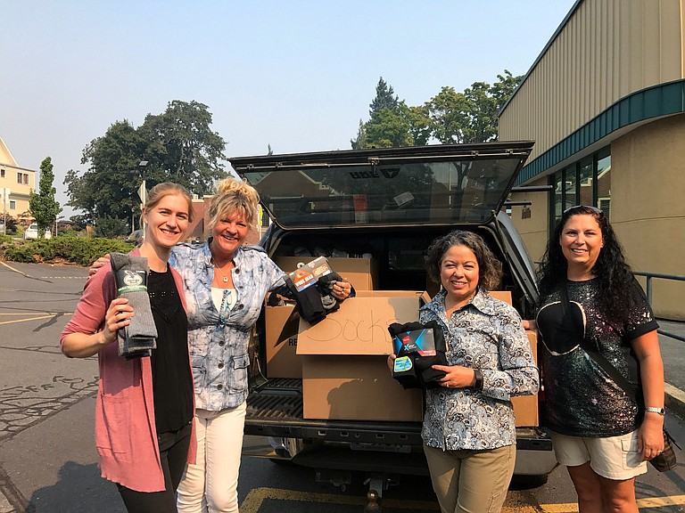 Janice Bell with Arome, Suzette Gehring and Chelsea Marr with Hood River News, and donation coordinator Terina Neal prepare donations for their trip to the Odell fire camp.