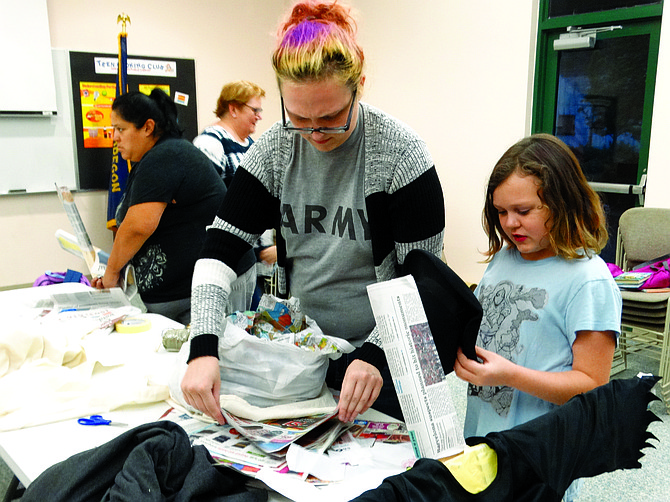 Amber Katausky and Willow Stewart, 8, work on stuffing a head for their scarecrow-witch on Monday.