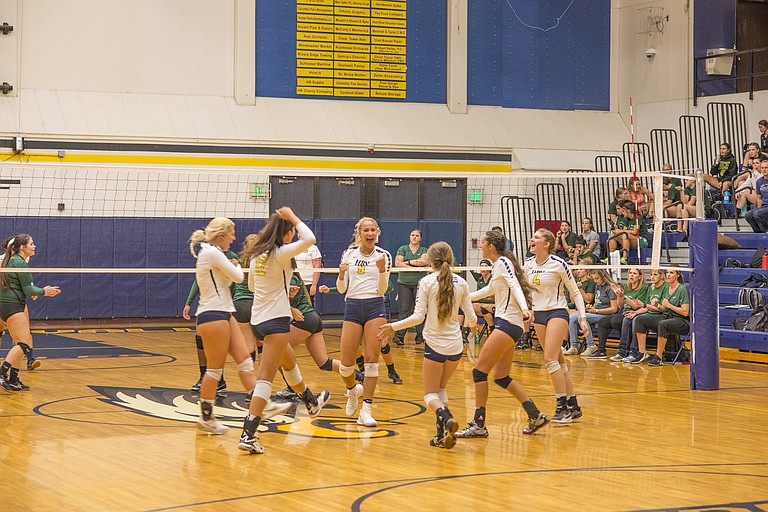 Katie Kennedy (above, 9), celebrates with her team after getting the first kill of the game in last week's matchup against Pendleton.