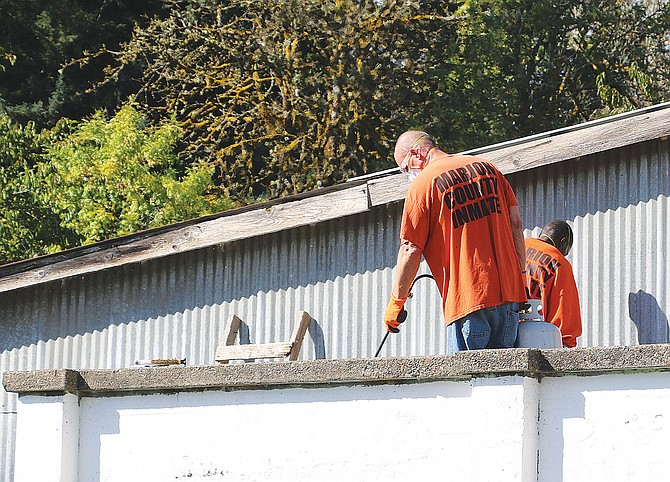 Marion County inmates work on the old Falls City's old jail building on Friday.
