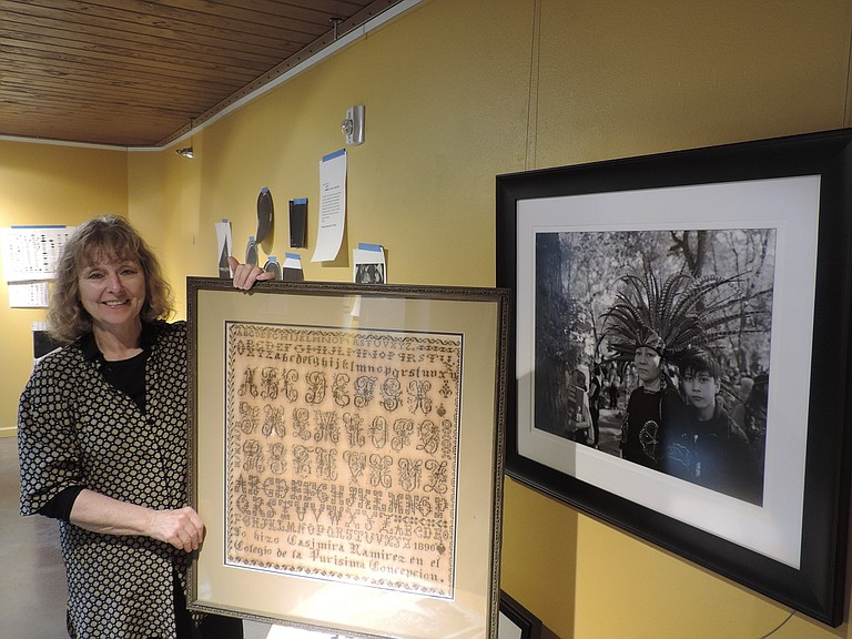 1890 needlepoint in Spanish, held by Museum director Lynn Orr, is part of Latino Experience exhibit.