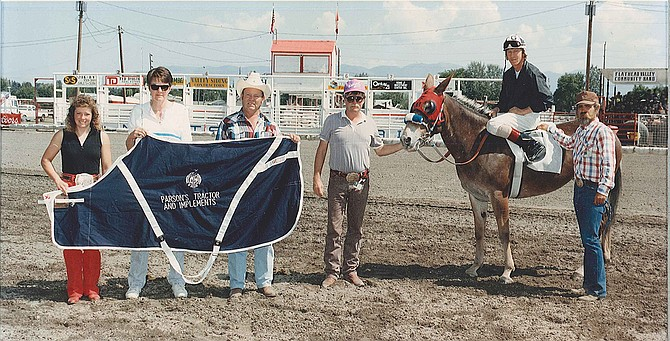 Racing mule Molly Bee following her win in the 350-yard course, at 21.73, on Aug. 16, 1991, at the N.W. Montana Fairgrounds. Barney Chambers is at far right.