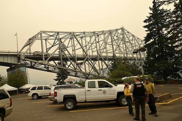 RESPONDERS confer next to Bridge of Gods as smoke covers the western Gorge, Sept. 4.