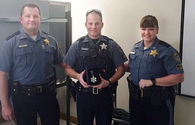 Oregon State Police Senior Trooper Zach Bohince, center, is pictured receiving the Oregon State Police Medal of Valor. At left is OSP Superintendent Travis Hampton and at right is Deputy Superintendent Terri Davie. The newly established medal is awarded to members who react to a situation by displaying acts of courage, which go beyond their normal duty, therefore reducing the risk of injury or loss of life to another person.