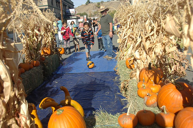A youngster enjoys playing a game of pumpkin bowling at 2016 Harvest Festival.