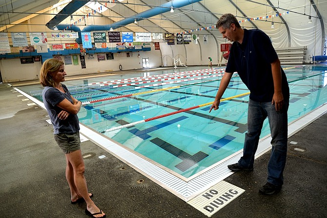 MARCIE WILY and Mark Hickok with Hood River Valley Parks and Recreation District stand before the pool at Hood River Aquatic Center in September. Hickok demonstrates the pool's filter system.