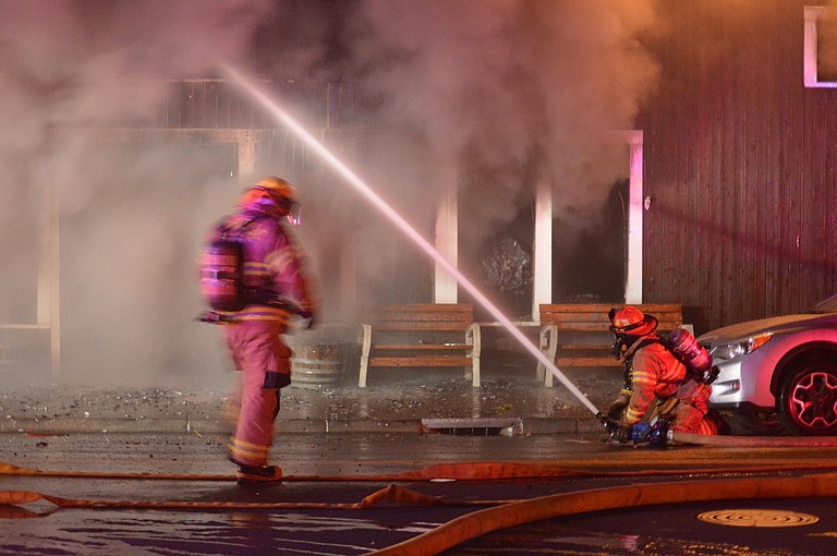 SMOKE billows in a surrealistic pattern in front of the building as firefighters battle Kayak Shed blaze on Sept. 27.