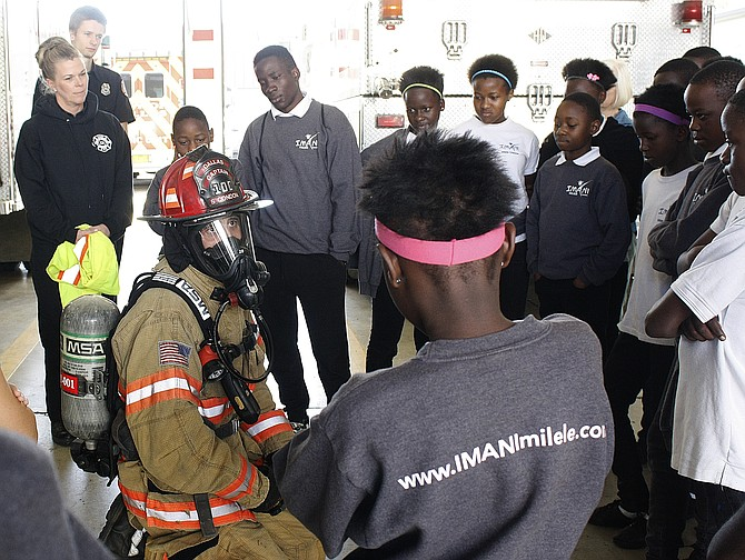 Dallas Fire & EMS volunteer firefighter Sean Condon explains to members of the Imani Milele Children's Choir what firefighters wear when they are working.