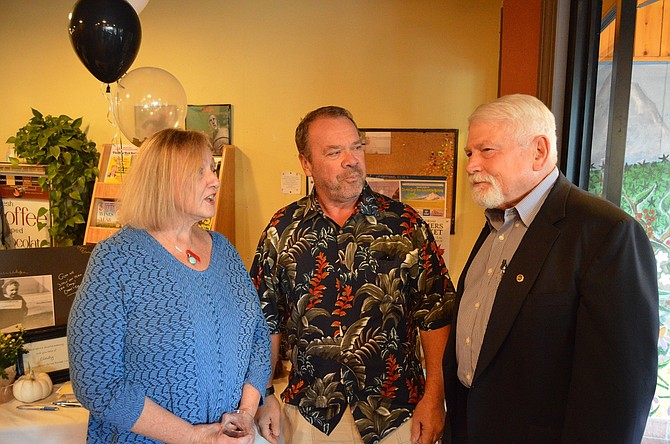 OUTGOING City Planning Director Cindy Walbridge talks  with Dave Smock, former city public works foreman and Hood River attorney Will Carey, at a reception in her honor Wednesday at Dog River Coffee. Carey serves as municipal judge in addition to his private practice.