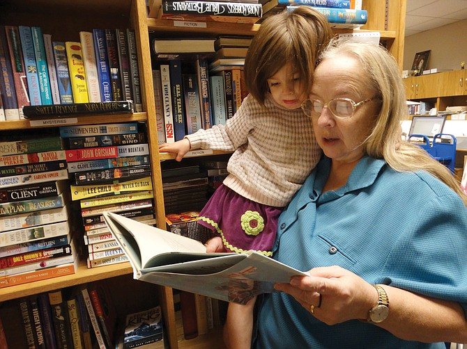 Carol Christ reads to her granddaughter Finley Christ, 3, from one of the books that will be on sale this weekend.