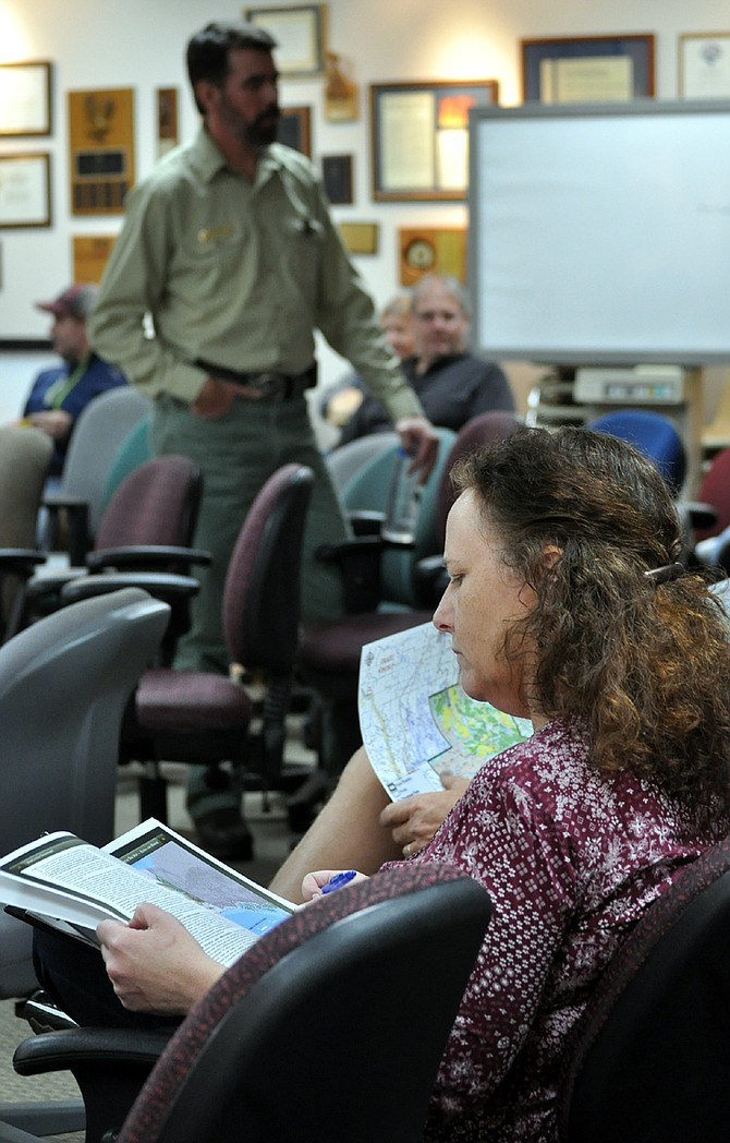A woman reviews documents prior to the Thursday, Oct. 5, meeting on the proposed End of the World project, held at the Nez Perce-Clearwater National Forests Office in Grangeville. Talking with attendees in back is Salmon River District Ranger Jeff Shinn.