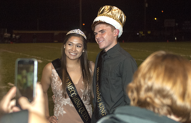 Homecoming Queen Alexia Tapia, left, and King Quinn Strassheim smile for pictures after being crowned during halftime of The Dalles High School's homecoming football game Friday, Oct. 6, at the Wahtonka Campus.
