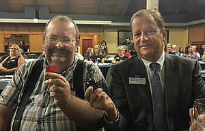 Eric Nisley, right, holds the glass cherry he was awarded at a recent ceremony recognizing employers who hire those with intellectual/developmental disabilities. At his left is employee Kurt Cochran, who began working for the DA's office in July to help digitize case files.