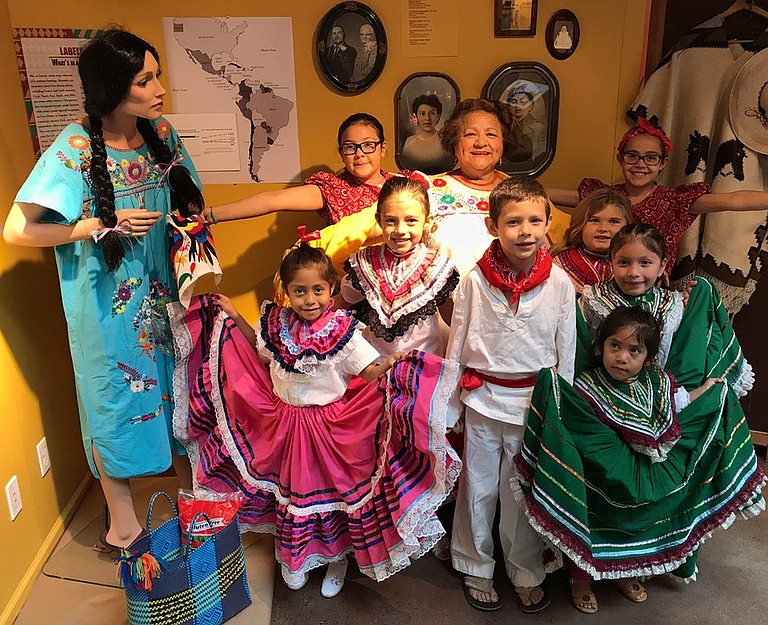 FOLKLORICO dancers, and 'Sharing History' exhibit surround long-time teacher Sandy Salazar at the exhibit opening at The History Museum of Hood River County.