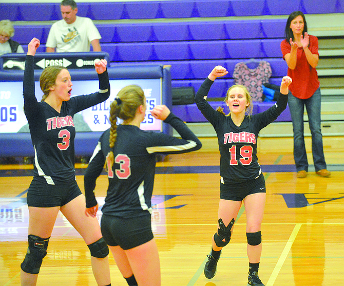 Republic's Carlie Rittel (3), Kailee Rittel (13), Summer Jones (19) and coach Andrea Hartwig celebrate point during match against Pateros on Oct. 10.