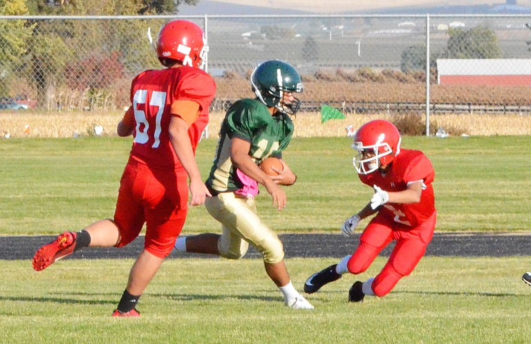 Ethan Christensen and Reyden Huizar of Housel Middle School's football team move in on the Sierra Vista Middle School ball carrier during yesterday's game. The Prosser team defeated the Sunnyside team, 12-0.