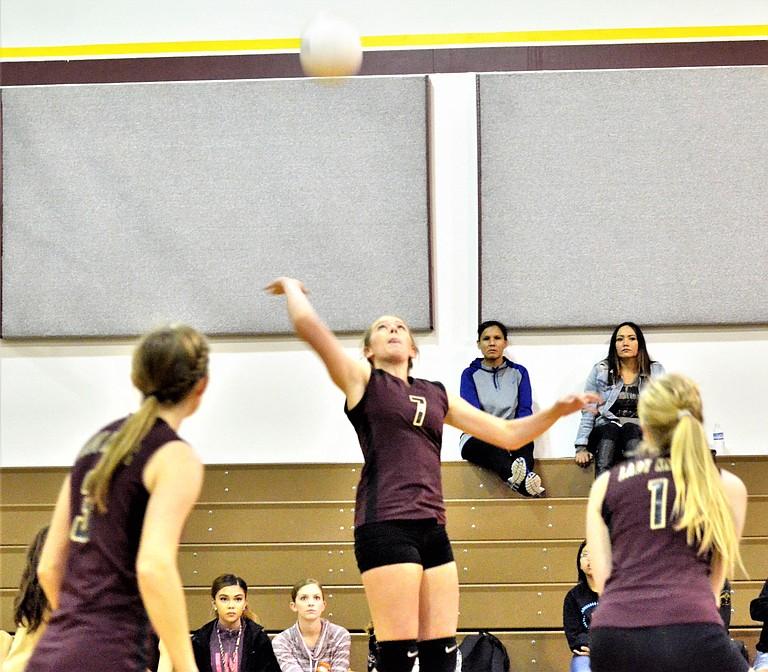 Kayla Van Wieringen of the Knights spikes the ball as teammates Alyssa Martin and Emily Broersma watch the shot.