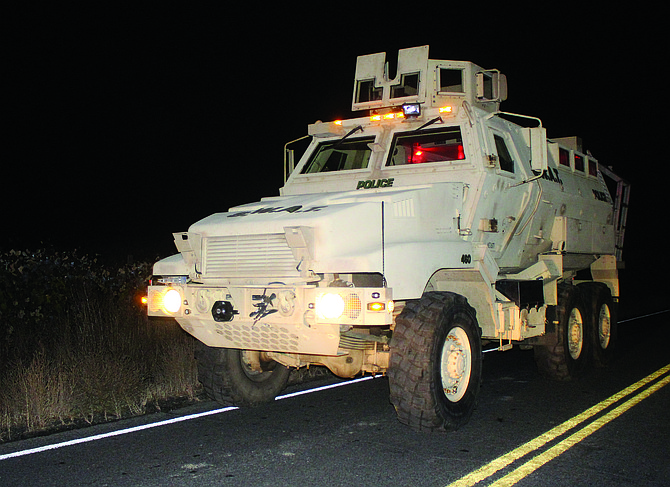 An armored police vehicle moves along Forsell Road during the overnight manhunt.