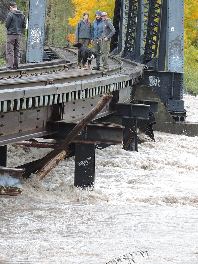 RIVER watchers stand on Mt. Hood Railroad trestle Sunday at noon as the Hood River nears crest stage. (The trestle is hazardous for pedestrians and is officially off-limits.)