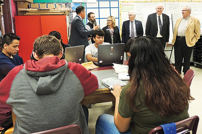 Students in Rosa Aviles's class continue while Superintendent Henry Strom and high school Principal Kim Casey give a school tour to, from left, legislators David Taylor, Bruce Chandler, Jim Honeyford and Norm Johnson.