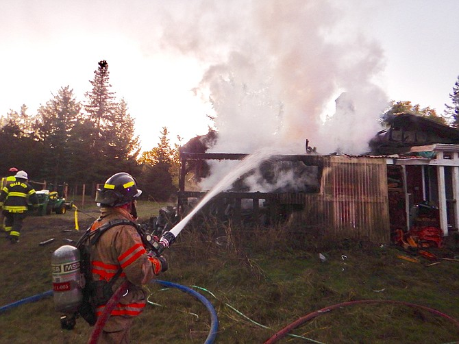 A firefighter battles a house fire in the 1800 block of Rueben Boise Road on Tuesday night.