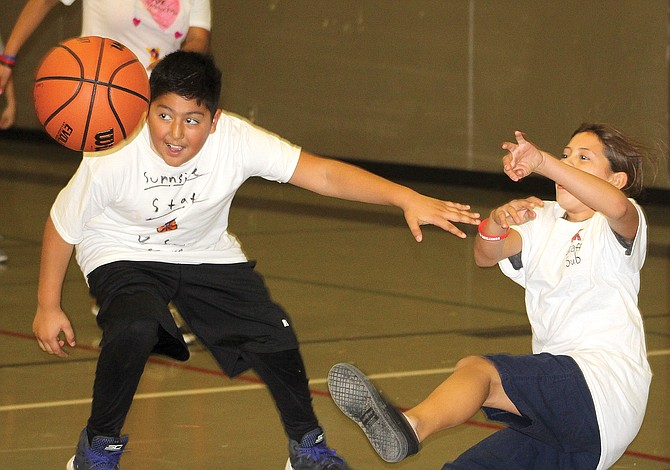 Chief Kamiakin Elementary School students and staff squared off in a game of hoops last night to raise money for student government. Pictured, student Ebony Ramirez, right, goes flying backwards after leaping for a rebound as Andre Rodriguez looks up-court. Playing with the staff team, Ramirez wasn't able to help teachers enough, as the student team held on to win.