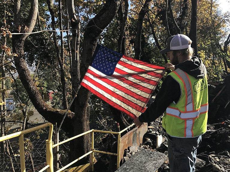 BEAM employee Billy Broderick pulled the shop's U.S. flag from the Kayak Shed fire. Demolition work is nearly complete at the site on Oak Street.