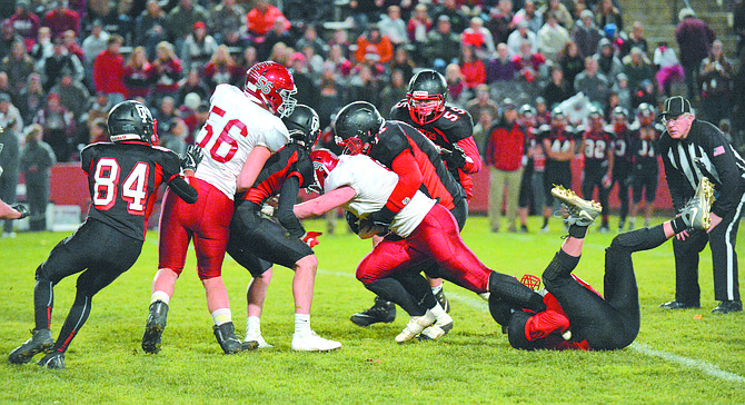 Omak tacklers attempt to take down Okanogan's Julian Cates in Backyard Brawl on Oct. 26.
